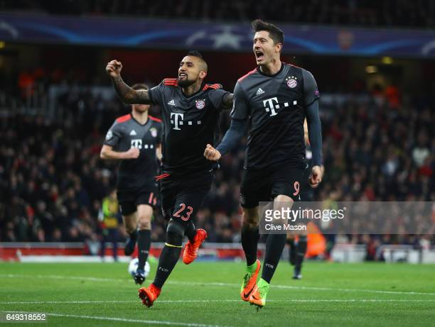 Robert Lewandowski of Bayern Muenchen celebrates with team mate Arturo Vidal as he scores their first goal from a penalty during the UEFA Champions...