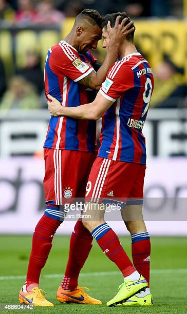 Robert Lewandowski of Bayern Muenchen celebrates with team mate Jerome Boateng after scoring his teams first goal during the Bundesliga match between...