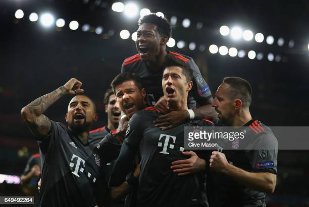 Robert Lewandowski of Bayern Muenchen celebrates with team mates as he scores their first goal from a penalty during the UEFA Champions League Round...