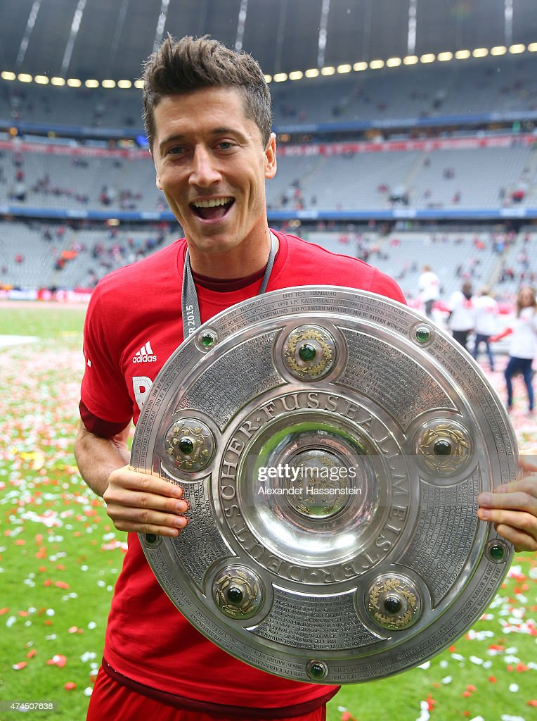 Robert Lewandowski of Bayern Muenchen celebrates with the trophjy after winning the league during the Bundesliga match between FC Bayern Muenchen and...