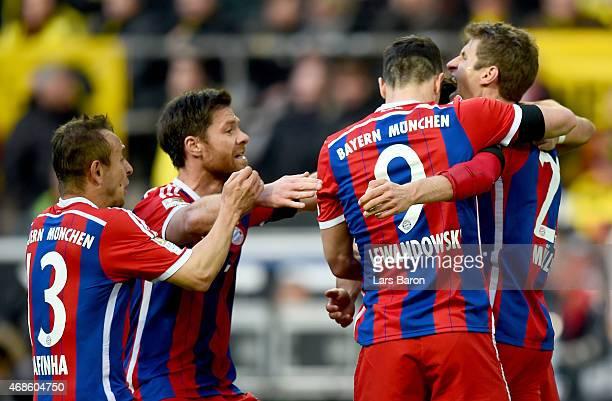 Robert Lewandowski of Bayern Muenchen celebrates with Thomas Muller of Bayern Muenchen and other team mates after scoring his teams first goal during...