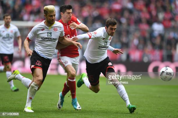Robert Lewandowski of Bayern Muenchen challenges Alexander Hack and Stefan Bell of 1 FSV Mainz 05 during the Bundesliga match between Bayern Muenchen...