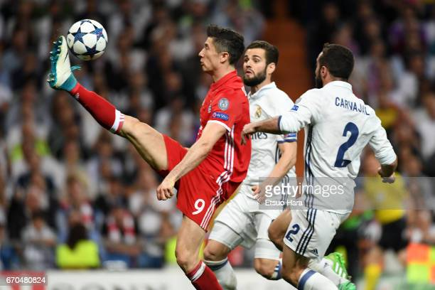 Robert Lewandowski of Bayern Muenchen controls the ball under pressure of Nacho and Dani Carvajal of Real Madrid during the UEFA Champions League...