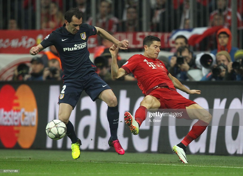 Robert Lewandowski (R) of Bayern Muenchen fights for the ball with Diego Godin of Atletico Madrid during the Champions League semi final second leg match between FC Bayern Muenchen and Club Atletico de Madrid at Allianz Arena on May 3, 2016 in Munich, Germany.