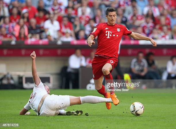 Robert Lewandowski of Bayern Muenchen fights for the ball with JanIngwer CallsenBracker of FC Augsburg during the Bundesliga match between FC Bayern...