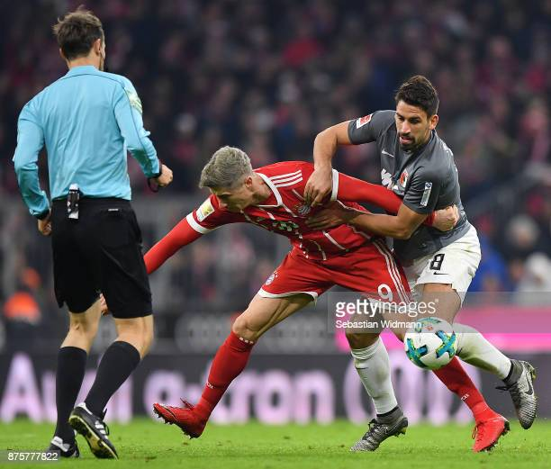 Robert Lewandowski of Bayern Muenchen fights for the ball with Rani Khedira of Augsburg during the Bundesliga match between FC Bayern Muenchen and FC...