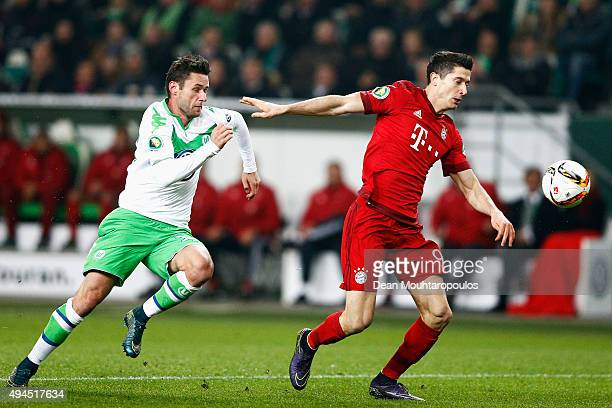 Robert Lewandowski of Bayern Muenchen gets past the trackle from Christian Trasch of VfL Wolfsburg during the DFB Cup match between VfL Wolfsburg and...