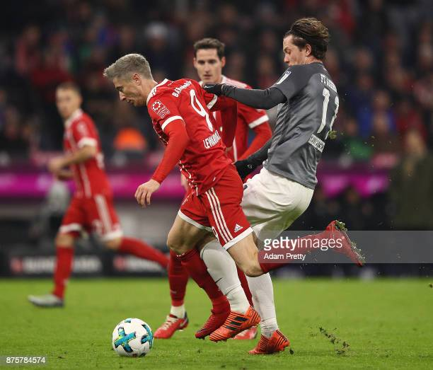 Robert Lewandowski of Bayern Muenchen is chased by Michael Gregoritsch of Augsburg during the Bundesliga match between FC Bayern Muenchen and FC...