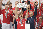 Robert Lewandowski of Bayern Muenchen lifts the Meisterschale as players and staffs celebrate the Bundesliga champions after the Bundesliga match...