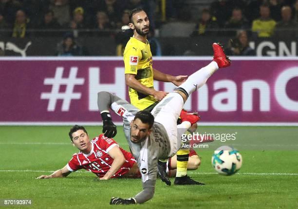 Robert Lewandowski of Bayern Muenchen Oemer Toprak of Dortmund and Roman Buerki of Dortmund look after the ball as Muenchen score their third goal to...