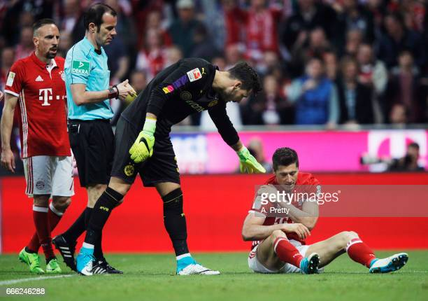 Robert Lewandowski of Bayern Muenchen receives an appology from Roman Buerki of Borussia Dortmund after injuring his shoulder during the Bundesliga...