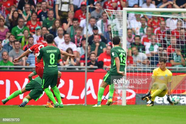 Robert Lewandowski of Bayern Muenchen scored his teams second goal to make it 20 past goalkeeper Jiri Pavlenka of Bremen during the Bundesliga match...