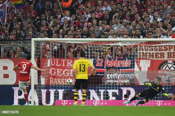 Robert Lewandowski of Bayern Muenchen scores his sides fourth goal from the penalty spot during the Bundesliga match between Bayern Muenchen and...