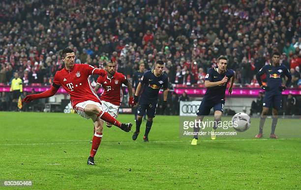 Robert Lewandowski of Bayern Muenchen scores his sides third goal from the penalty spot during the Bundesliga match between Bayern Muenchen and RB...
