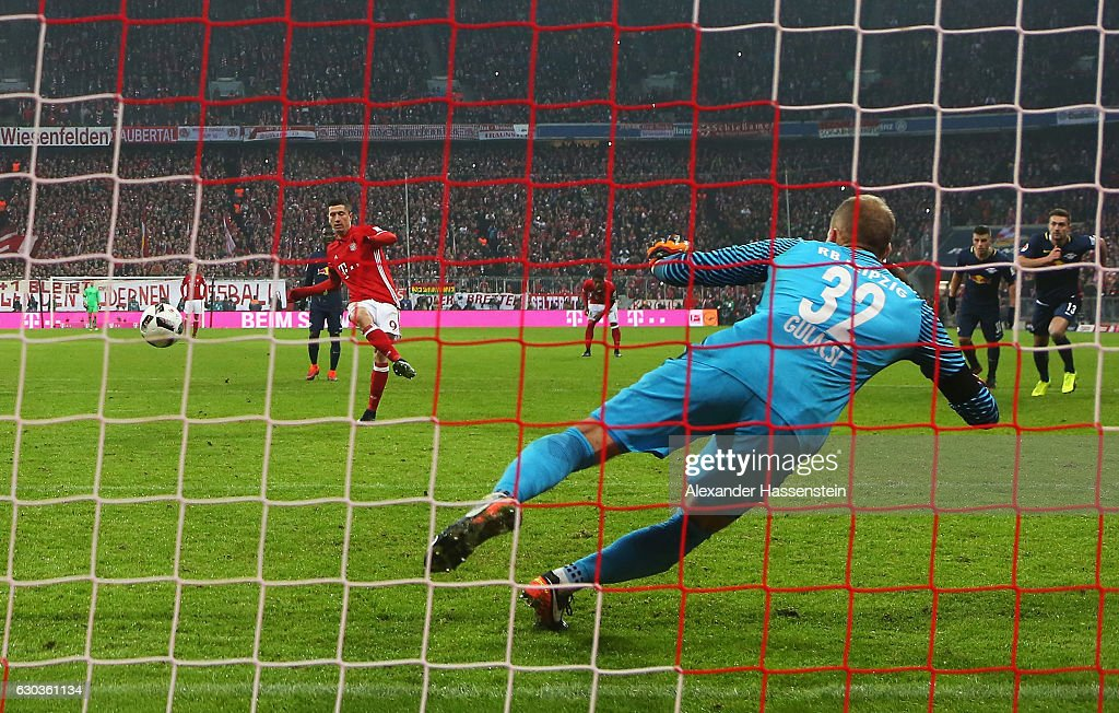 Robert Lewandowski of Bayern Muenchen (L) scores his sides third goal from the penalty spot past Peter Gulacsi of RB Leipzig (R) during the Bundesliga match between Bayern Muenchen and RB Leipzig at Allianz Arena on December 21, 2016 in Munich, Germany.