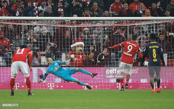 Robert Lewandowski of Bayern Muenchen scores his sides third goal from the penalty spot past Peter Gulacsi of RB Leipzig during the Bundesliga match...