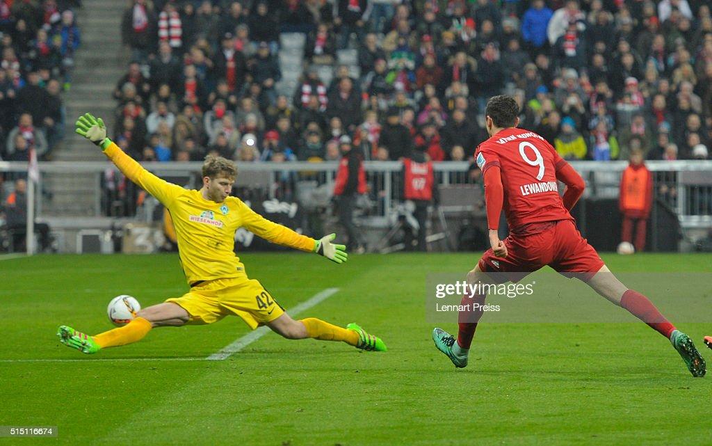 Robert Lewandowski of Bayern Muenchen scores his team's fourth goal against Felix Wiedwald of Werder Bremen during the Bundesliga match between FC...