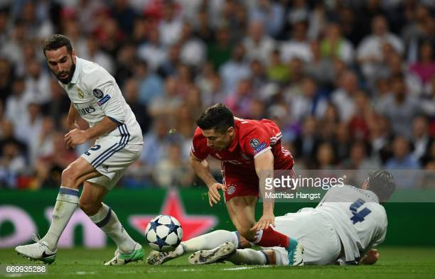 Robert Lewandowski of Bayern Muenchen Sergio Ramos of Real Madrid and Daniel Carvajal of Real Madrid compete for the ball during the UEFA Champions...