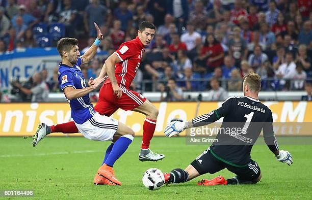 Robert Lewandowski of Bayern Muenchen shoots wide as Ralf Fahrmann of Schalke attepts to save during the Bundesliga match between FC Schalke 04 and...