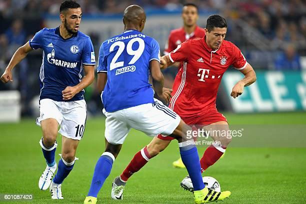 Robert Lewandowski of Bayern Muenchen takes on Naldo of Schalke during the Bundesliga match between FC Schalke 04 and Bayern Muenchen at VeltinsArena...