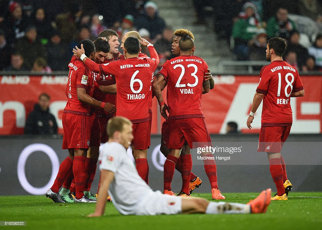 Robert Lewandowski of Bayern Munich (2L) celebrates with team mates as he scores their first goal during the Bundesliga match between FC Augsburg and FC Bayern Muenchen at SGL Arena on February 14, 2016 in Augsburg, Germany.