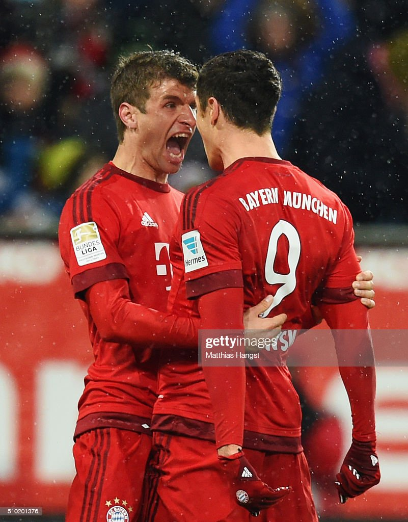 Robert Lewandowski of Bayern Munich (9) celebrates with Thomas Mueller as he scores their first goal during the Bundesliga match between FC Augsburg and FC Bayern Muenchen at SGL Arena on February 14, 2016 in Augsburg, Germany.