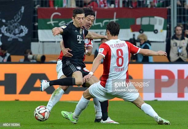 Robert Lewandowski of Bayern Munich in action against JeongHo Hong and Markus Feulner of FC Augsburg during the Bundesliga soccer match between FC...