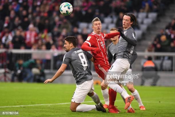 Robert Lewandowski of Bayern Munich in action against Rani Khedira and Michael Gregoritsch of Augsburg during the Bundesliga soccer match between FC...