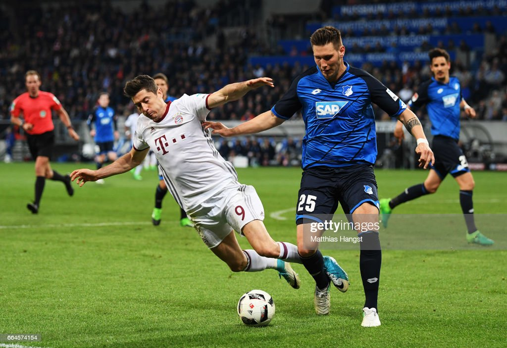 Robert Lewandowski of Bayern Munich is challenged by Niklas Suele of 1899 Hoffenheim during the Bundesliga match between TSG 1899 Hoffenheim and Bayern Muenchen at Wirsol Rhein-Neckar-Arena on April 4, 2017 in Sinsheim, Germany.