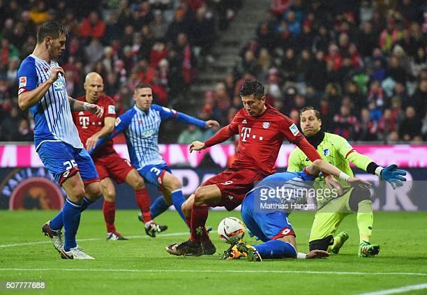 Robert Lewandowski of Bayern Munich is foiled by Ermin Bicakcic and Oliver Baumann of Hoffenheim during the Bundesliga match between FC Bayern...