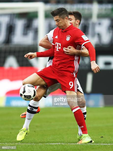 Robert Lewandowski of Bayern Munich is tackled by Nico Elvedi of Borussia Moenchengladbach during the Bundesliga match between Borussia...
