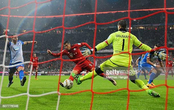 Robert Lewandowski of Bayern Munich scores their first goal past goalkeeper Oliver Baumann of Hoffenheim during the Bundesliga match between FC...