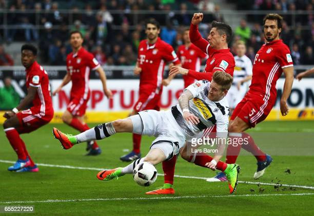 Robert Lewandowski of Bayern Munich tackles Andre Hahn of Borussia Moenchengladbach during the Bundesliga match between Borussia Moenchengladbach and...