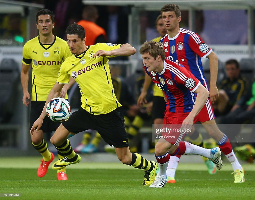 Robert Lewandowski (l) of Borussia Dortmund battles for the ball with Toni Kroos (r) of Bayern Muenchen during the DFB Cup Final match between Borussia Dortmund and FC Bayern Muenchen at Olympiastadion on May 17, 2014 in Berlin, Germany.