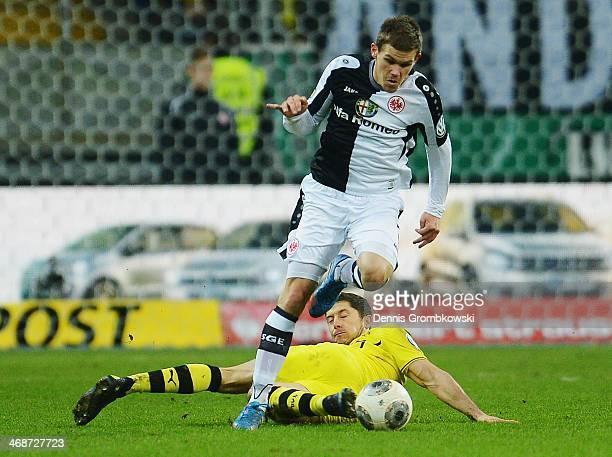 Robert Lewandowski of Borussia Dortmund challenges Sebastian Jung of Eintracht Frankfurt during the DFB Cup quarterfinal match between Eintracht...