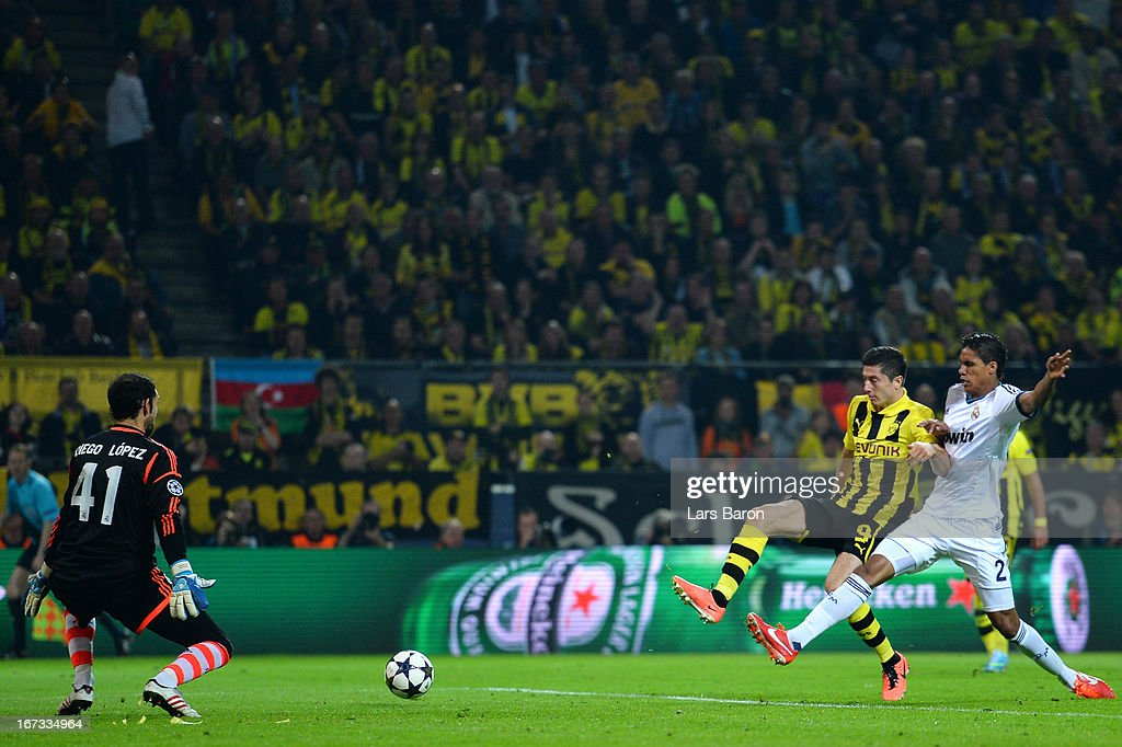 Robert Lewandowski of Borussia Dortmund scores his team's second goal despite the challenge from Raphael Varane of Real Madridduring the UEFA Champions League semi final first leg match between Borussia Dortmund and Real Madrid at Signal Iduna Park on April 24, 2013 in Dortmund, Germany.