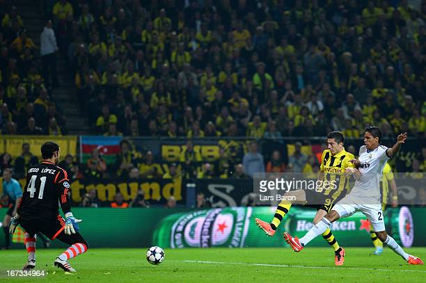 Robert Lewandowski of Borussia Dortmund scores his team's second goal despite the challenge from Raphael Varane of Real Madridduring the UEFA...
