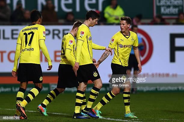 Robert Lewandowski of Dortmund celebrates his team's third goal with team mates PierreEmerick Aubameyang Jakub Blaszczykowski and Erik Durm during...