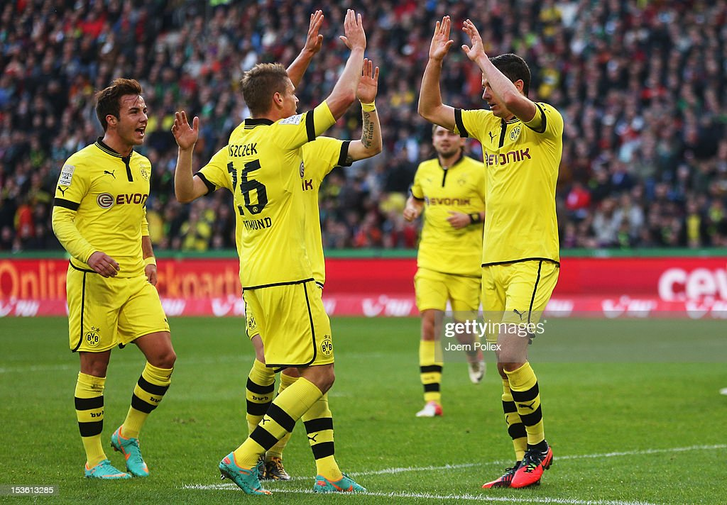 Robert Lewandowski of Dortmund celebrates with his team mates after scoring his team's first goal during the Bundesliga match between Hannover 96 and...