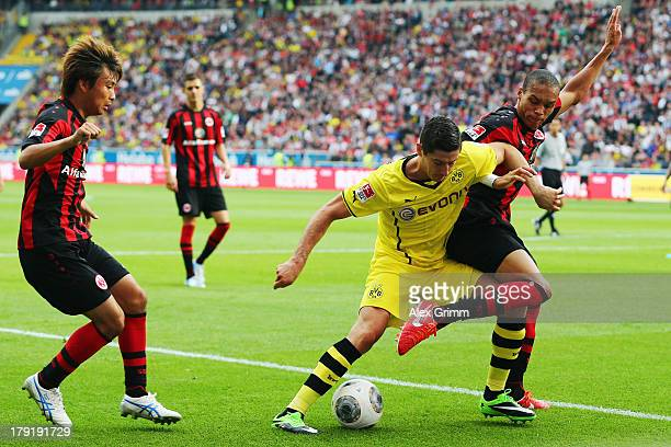 Robert Lewandowski of Dortmund is challenged by Bamba Anderson and Takashi Inui of Frankfurt during the Bundesliga match between Eintracht Frankfurt...