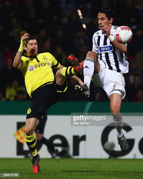 Robert Lewandowski of Dortmund is challenged by Benjamin Huebner of Aalen during the second round match of the DFB Cup between VfR Aalen and Borussia...
