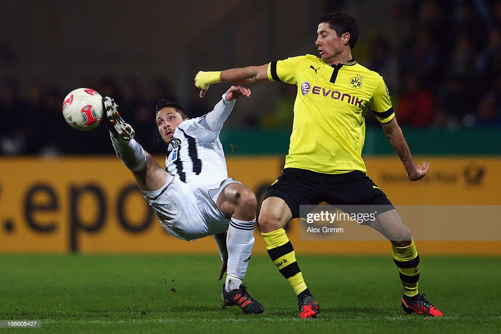 Robert Lewandowski of Dortmund is challenged by Tim Kister of Aalen during the second round match of the DFB Cup between VfR Aalen and Borussia...