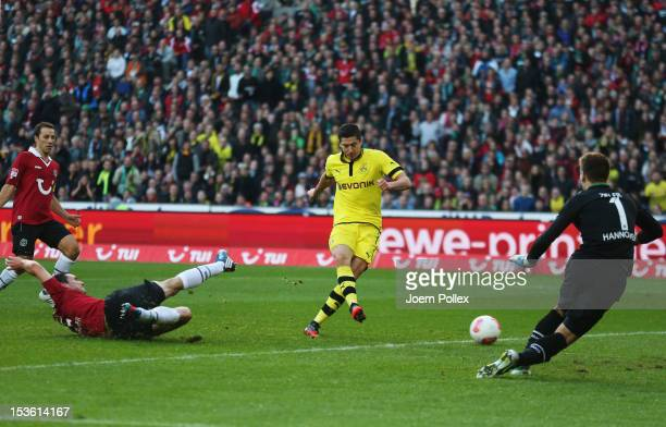 Robert Lewandowski of Dortmund scores his team's first goal during the Bundesliga match between Hannover 96 and Borussia Dortmund at AWD Arena on...