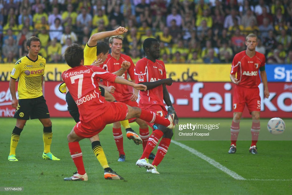 <a gi-track='captionPersonalityLinkClicked' href=/galleries/search?phrase=Robert+Lewandowski&family=editorial&specificpeople=5532633 ng-click='$event.stopPropagation()'>Robert Lewandowski</a> of Dortmund (C) scores the first goal against <a gi-track='captionPersonalityLinkClicked' href=/galleries/search?phrase=Hajime+Hosogai&family=editorial&specificpeople=4023693 ng-click='$event.stopPropagation()'>Hajime Hosogai</a> and Gibril Sankoh (R) during the Bundesliga match between Borussia Dortmund and FC Ausgburg at Signal Iduna Park on October 1, 2011 in Dortmund, Germany.