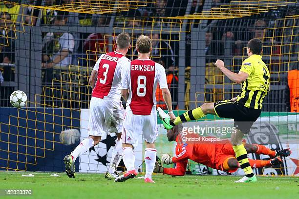 Robert Lewandowski of Dortmund scores the first goal against Kenneth Vermeer Toby Alderweireld and Chrisitian Eriksen of Amsterdam during the UEFA...