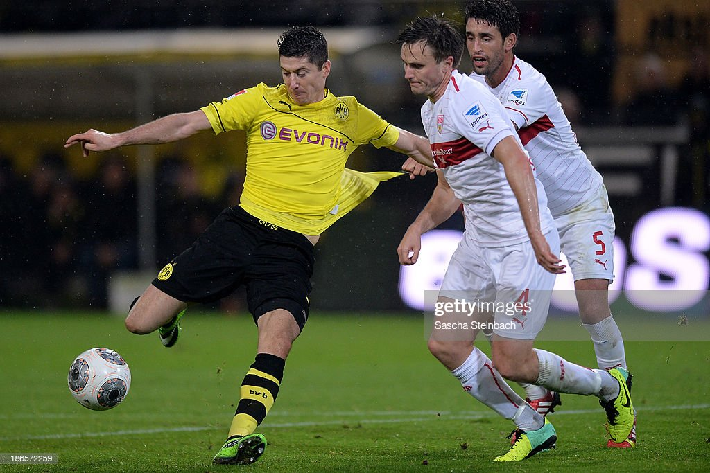 <a gi-track='captionPersonalityLinkClicked' href=/galleries/search?phrase=Robert+Lewandowski&family=editorial&specificpeople=5532633 ng-click='$event.stopPropagation()'>Robert Lewandowski</a> of Dortmund vies with <a gi-track='captionPersonalityLinkClicked' href=/galleries/search?phrase=William+Kvist&family=editorial&specificpeople=2465270 ng-click='$event.stopPropagation()'>William Kvist</a> and <a gi-track='captionPersonalityLinkClicked' href=/galleries/search?phrase=Karim+Haggui&family=editorial&specificpeople=542358 ng-click='$event.stopPropagation()'>Karim Haggui</a> of Stuttgart and scores his team's 3rd goal during the Bundesliga match between Borussia Dortmund and VfB Stuttgart at Signal Iduna Park on November 1, 2013 in Dortmund, Germany.