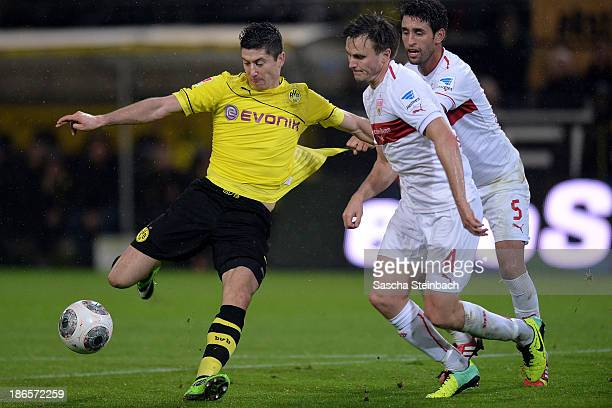 Robert Lewandowski of Dortmund vies with William Kvist and Karim Haggui of Stuttgart and scores his team's 3rd goal during the Bundesliga match...