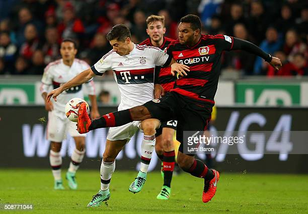 Robert Lewandowski of FC Bayern Muenchen battles for the ball with Jonathan Tah of Bayer Leverkusen during the Bundesliga match between Bayer...
