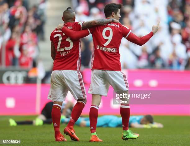Robert Lewandowski of FC Bayern Muenchen celebrates his first goal with teammate Arturo Vidal as goalkeeper Lukas Hradecky of Eintracht Frankfurt...