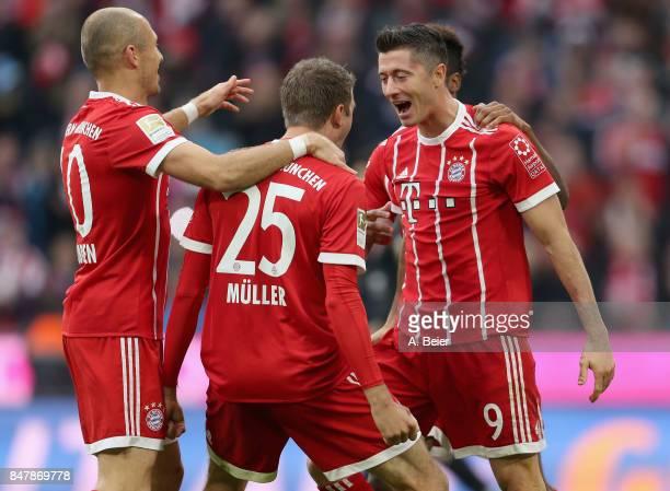 Robert Lewandowski of FC Bayern Muenchen celebrates his first goal with teammates Thomas Mueller and Arjen Robben during the Bundesliga match between...